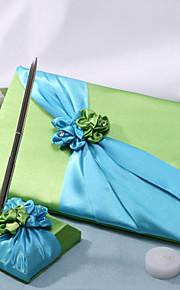 vert livre d'or de mariage et un stylo serti de fleurs vertes et bleues signer dans le livre
